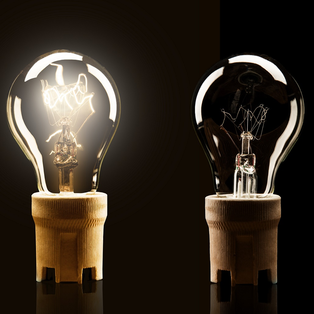 two light bulbs against a black background, one turned on and one turned off